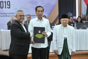 Ketua KPU Arief Budiman menyerahkan salinan Keputusan KPU tentang Penetapan Paslon Presiden dan Wapres Terpilih Pemilu 2019 kepada Paslon Terpilih Jokowi dan Ma'ruf Amin, di Kantor KPU, Jakarta, Minggu (30/6) sore. (Foto: Humas/Jay)