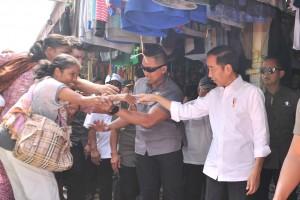 Presiden Jokowi melayani permintaan jabat tangan warga saat berkunjung ke Pasar Tradisional Onan Baru Pangururan, Kabupaten Samosir, Sumut, Rabu (31/7) siang. (Foto: JAY/Humas)
