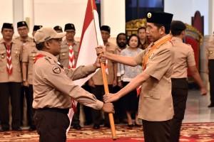 Presiden Jokowi menyerahkan bendera Merah Putih kepada ketua kontingan saar melepas delegasi Pramuka Indonesia pada Jambore Pramuka Dunia, di Istana Negara, Jakarta, Jumat (19/7) pagi. (Foto: Rahmat/Humas)
