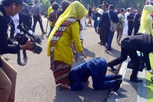 Seorang perwira remaja berlutur mencium kaki ibunya pada acara Pelantikan Perwira Remaja TNI dan Polri, di halaman Istana Merdeka, Jakarta, Selasa (16/7) pagi. (Foto: Rahmat/Humas)