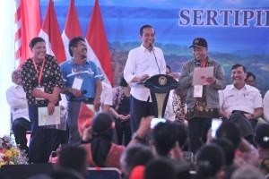 Presiden Jokowi tersenyum saat berdialog dengan warga pada penyerahan sertipikat tanah untuk rakyat, di Dermaga Ajibata, Kabupaten Toba Samosir, Sumut, Selasa (30/7) siang. (Foto: JAY/Humas)