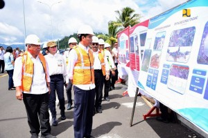 President Jokowi takes a closer look at the model of Manado-Bitung toll road when inspecting the project at Air Madidi Interchange, Bitung, North Sulawesi, Friday (5/7) (Photo: Ministry of PUPR)